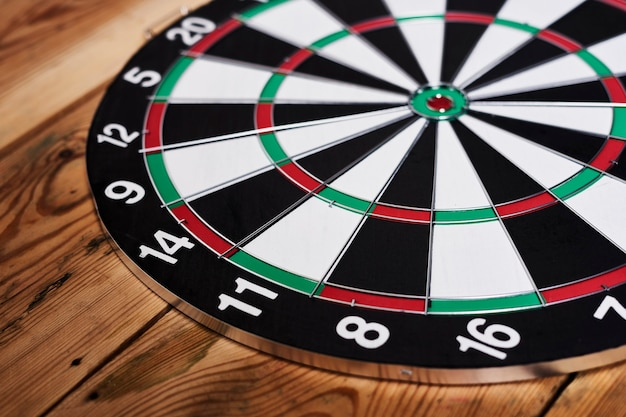 Closeup view of a dartboard lying on a wooden table