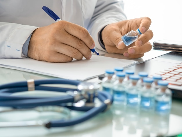 Closeup view of a doctors hands holding a test tube with modern vaccine