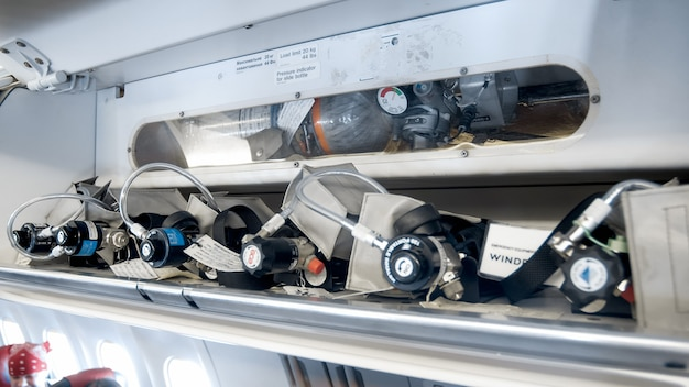 Closeup view of emergency rescue system and oxygen cylinders on passenger airplane.