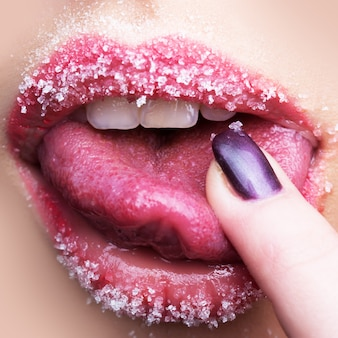Closeup view of facial body part of beautiful sexual open female lips with sugar icing lipstick and white teeth touching tongue with finger, square picture