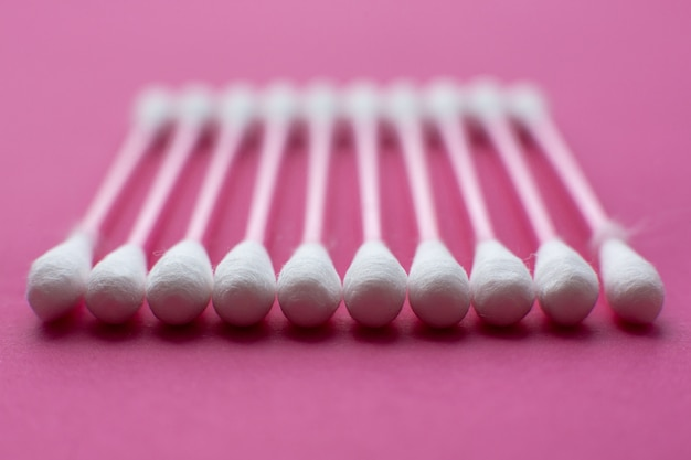 ピンクの背景に水平線で置かれた綿棒の上からのクローズアップビュー。