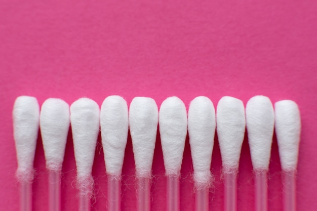 Closeup view from above on heads of cotton buds laid in a horizontal line on pink background