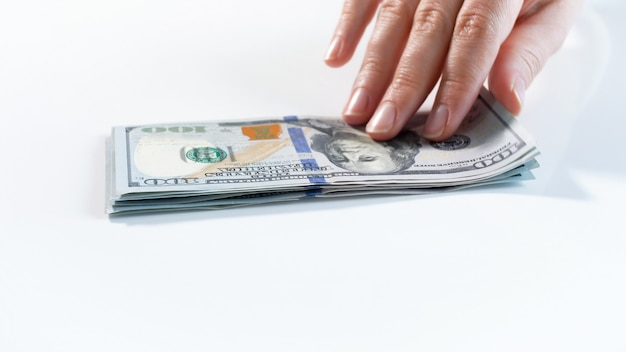 Closeup view of hand taking dollar banknote from stack of money on white desk.