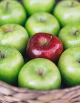 Closeup view of a healthy green apples and one red apple in a basket