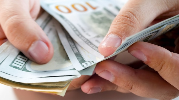 Closeup view of male businessman counting money in hands.