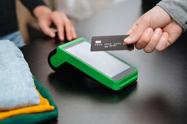 Closeup view, male customer using bank credit card for contactless payment by nfc terminal on counter while doing shopping in clothing store