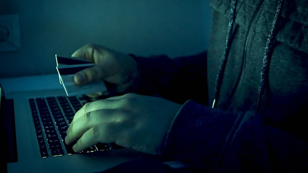 Closeup view of male hacker's hands holding credit cards and typing on laptop at night