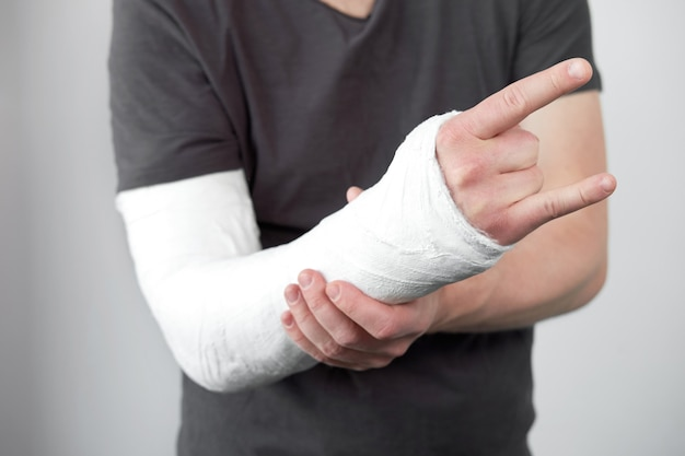 Closeup view of man's hand with plaster cast on a white wall background.