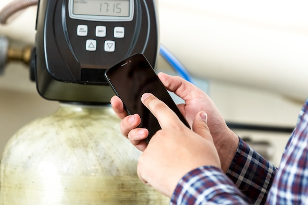 Closeup view of man typing factory equipment meter reading at smartphone