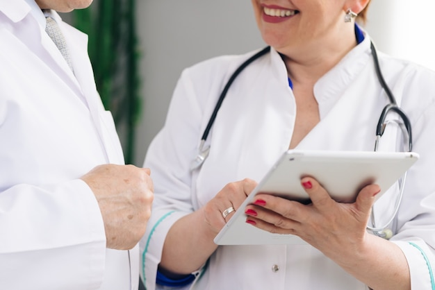 Closeup view of man and woman doctors using tablet during working day at clinic.