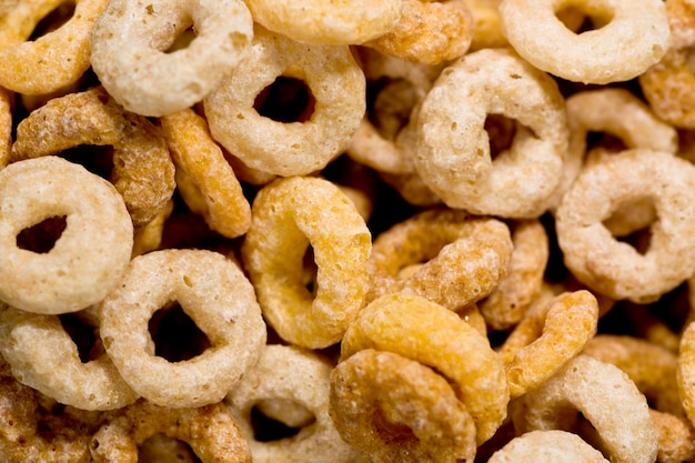 Closeup view of many donut shaped cereals on a bowl.
