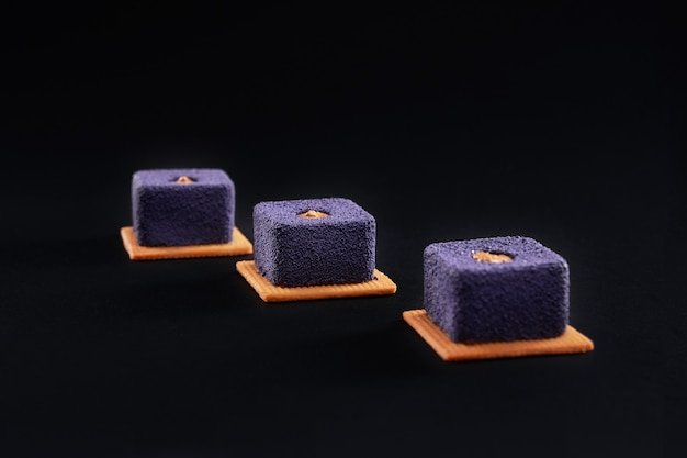 Closeup view of matte purple crunchy dessert filled with brown creme