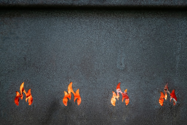 Closeup view of metal barbeque grill texture. red hot flames background.