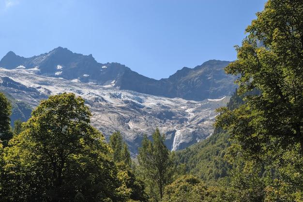 Крупным планом вид горы сцены и далеко водопад в национальном парке домбай, кавказ, россия, европа. летний пейзаж, солнечная погода и солнечный день