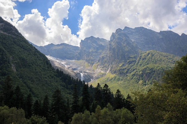 Closeup view mountains scenes and far away waterfall in national park dombai, caucasus, russia, europe. summer landscape, sunshine weather and sunny day
