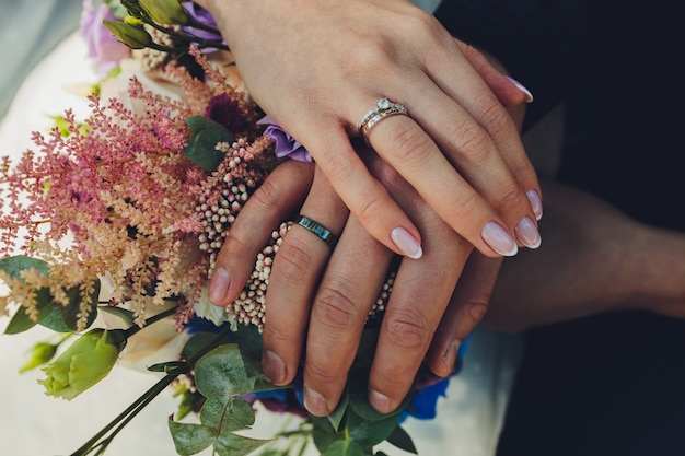 Closeup view of newlyweds hands holding colorful wedding bouquet