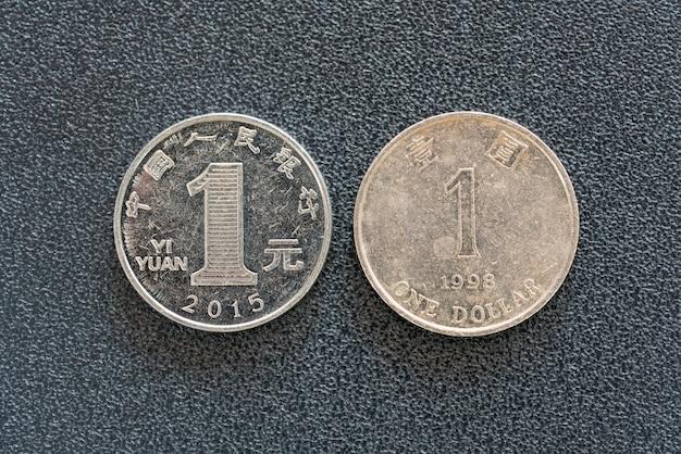어두운 배경에 1 중국 위안 및 1 달러 홍콩 동전의 근접 촬영보기.