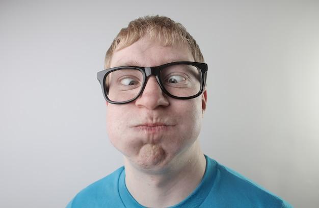 青いtシャツと眼鏡をかけて変な顔のジェスチャーをしている白人男性のクローズアップビュー