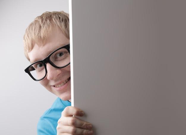 파란색 티셔츠와 재미 있은 얼굴 제스처를 만드는 안경을 착용하는 백인 남성의 근접 촬영보기