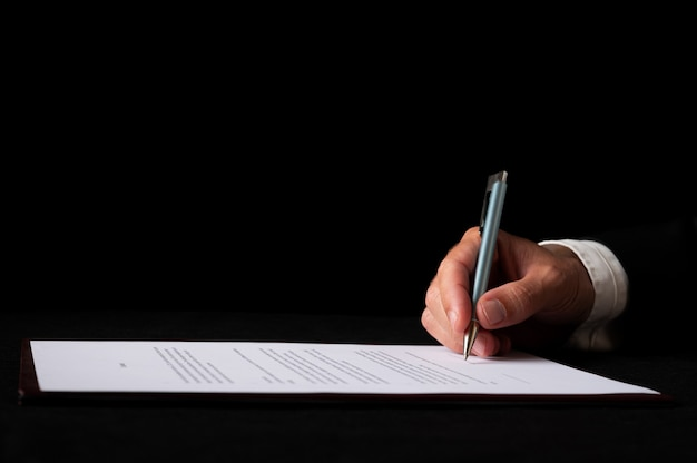 Крупным планом вид руки бизнесмена, подписывающего документ или контракт. на черном фоне.
