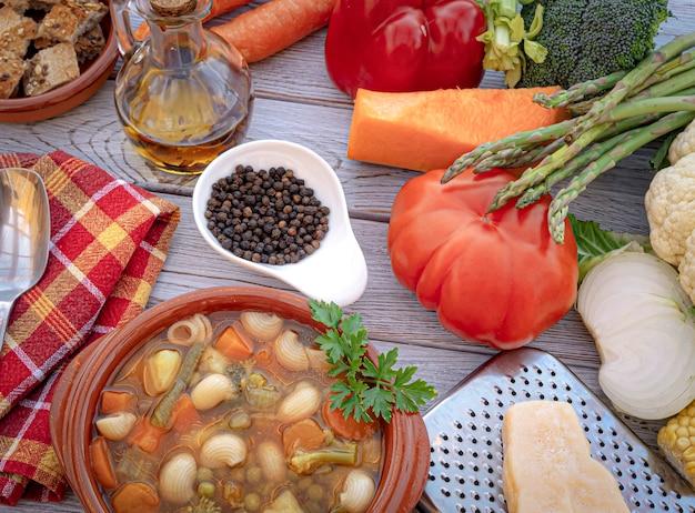 新鮮な、すぐに食べられる自家製野菜スープと木製のテーブルのクローズアップビュー。木製のテーブルに生野菜、黒胡椒、オリーブオイル、クルトン、パルメザンチーズ