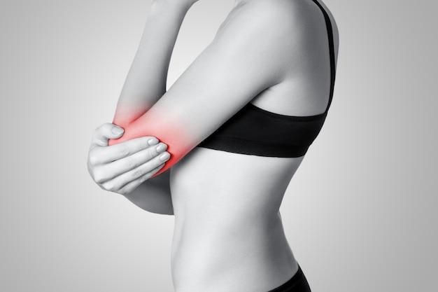 회색 배경에 팔꿈치 통증이 있는 젊은 여성의 근접 촬영 보기