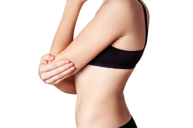 白い背景に肘の痛みを伴う若い女性のクローズアップビュー。
