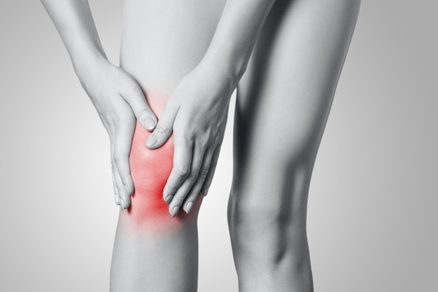 灰色の背景に膝の痛みを持つ若い女性のクローズアップビュー。赤い点のある白黒写真。