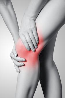 灰色の背景に膝の痛みがある若い女性のクローズアップビュー