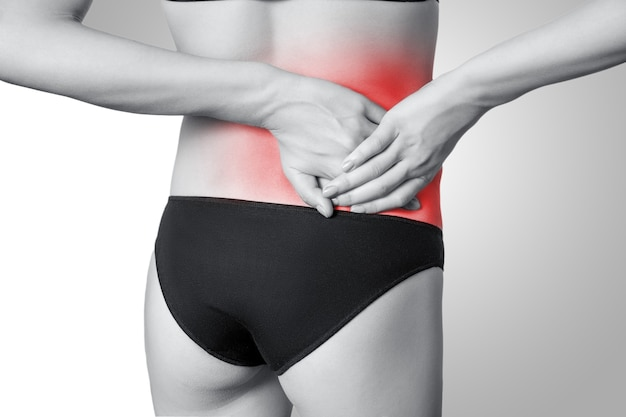 Крупным планом вид молодой женщины с болью в спине на сером фоне. черно-белое фото с красной точкой.