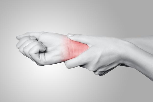 Крупным планом вид молодой женщины с болью под рукой на сером фоне