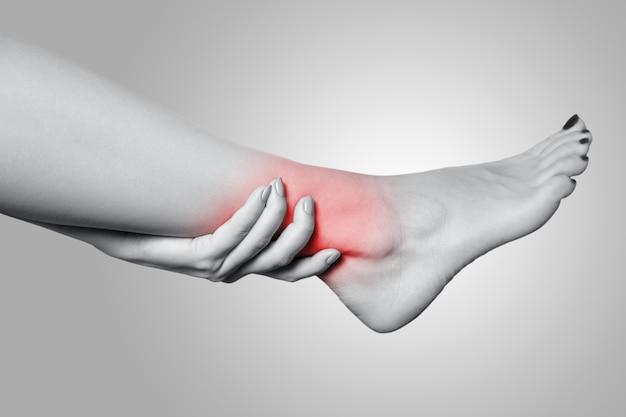 회색 배경에 다리에 통증이 있는 젊은 여성의 클로즈업 보기. 빨간 점이 있는 흑백 사진.