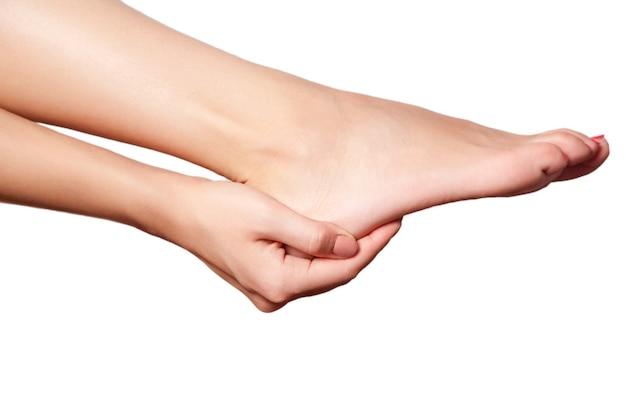흰색 바탕에 다리에 통증을 가진 젊은 여자의 근접 촬영 보기.