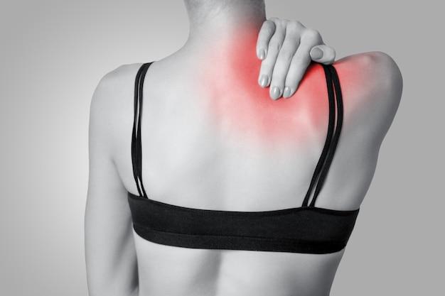 Крупным планом вид молодой женщины с болью в плече или шее на сером фоне. черно-белое фото с красной точкой.