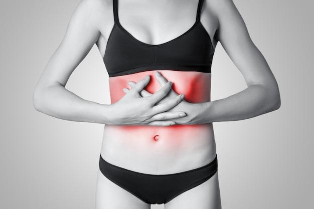 회색 배경에 복통이나 소화 또는 생리 주기가 있는 젊은 여성의 클로즈업 보기. 빨간 점이 있는 흑백 사진.