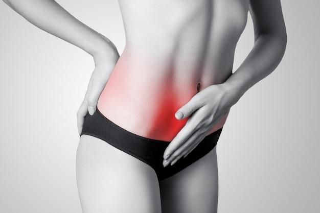 灰色の背景に胃の痛みまたは消化または周期周期を持つ若い女性のクローズアップビュー
