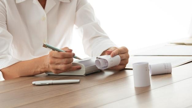 Крупным планом вид бухгалтера, проверяющего распечатку квитанции на счетной машине.