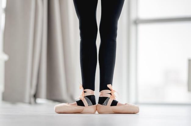 振り付けスタジオでのダンスクラス中に最初の位置にとどまっているバレリーナのまっすぐな脚のクローズアップビュー