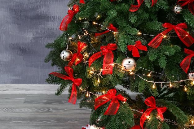 色の壁の背景に美しい装飾されたクリスマスツリーのクローズアップビュー