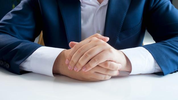 白いオフィスの机の上にahndsを保持している青いスーツを着たビジネスマンのクローズアップビュー。