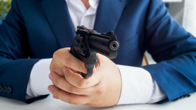 Крупным планом вид бизнесмена в костюме, сидящего за столом и целящегося с пистолетом