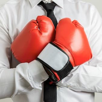 그의 팔을 가진 빨간 권투 장갑을 끼고 사업가의 근접 촬영보기는 그의 가슴에 건넜다.
