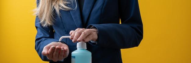 彼女の手に手の消毒剤を適用する実業家のクローズアップビュー