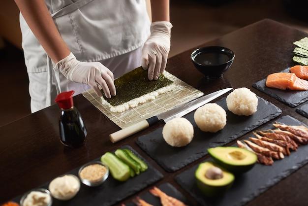 米、ノリ、アボカド、サーモン、醤油の材料で巻き寿司を準備するシェフの手のクローズアップビュー