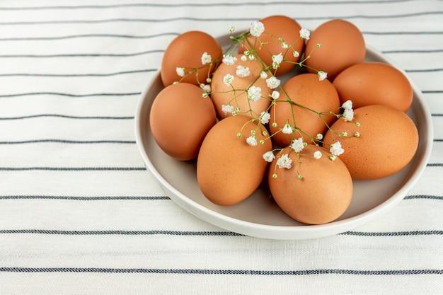 新鮮な自家製料理を調理するための多くの生の丸ごと茶色の鶏の卵でいっぱいの粘土プレートのクローズアップビュー。