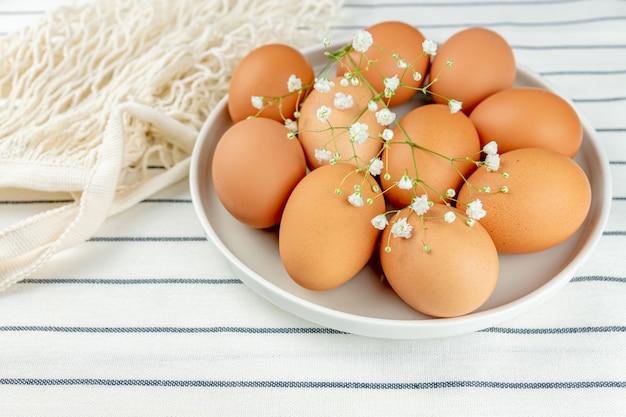 신선한 집에서 만든 음식을 요리에 대 한 많은 원시 전체 갈색 닭고기 달걀의 전체 클레이 접시의 근접 촬영보기.