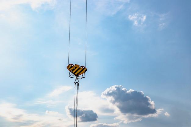 푸른 하늘에 대 한 크레인 후크의 근접 촬영 보기입니다.