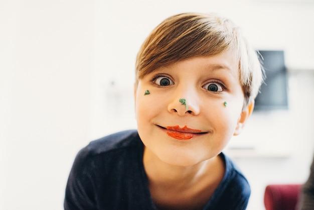 광대 입술로 웃고 있는 먹을 수 있는 밝은 색 크림으로 칠해진 얼굴을 가진 귀여운 소년의 클로즈업 보기
