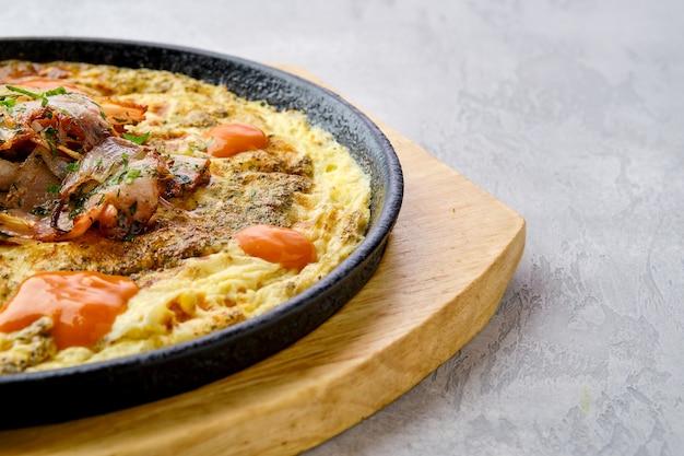 Крупным планом вид яиц с болгарским перцем и помидорами, запеченными в духовке на чугунной сковороде