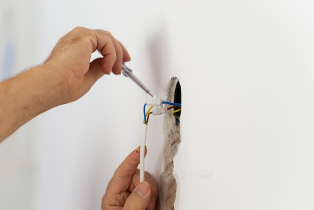 가정에서 와이어 회로에서 전류의 존재를 확인하는 전기의 근접 촬영보기.